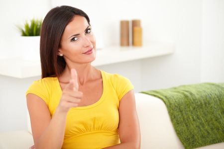 focus on the foreground: Beautiful young woman pointing at you while sitting on the couch - focus on foreground Stock Photo