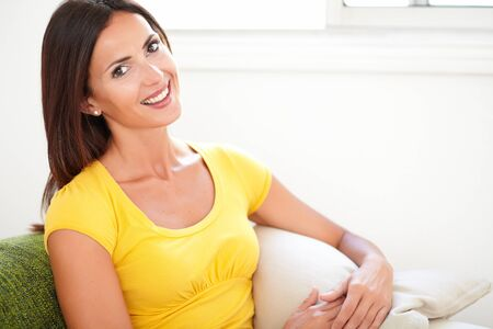 caucasian ethnicity: Young woman of caucasian ethnicity toothy smiling at the camera while sitting at home Stock Photo