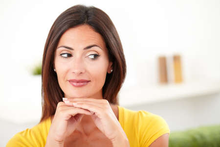 focus on the foreground: Young woman contemplating with both hands on her chin while looking away - focus on foreground Stock Photo