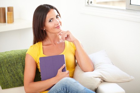 hand on the chin: Beautiful woman holding a tablet while sitting with one hand on her chin - indoors Stock Photo