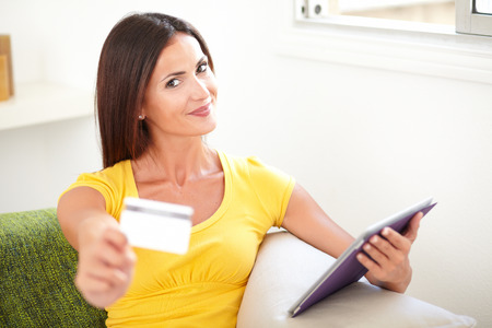 yellow shirt: Smiling woman in yellow shirt giving you a credit card while sitting inside the house