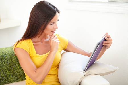 elevated view: Thoughtful woman with straight hair wondering while using a tablet - elevated view Stock Photo
