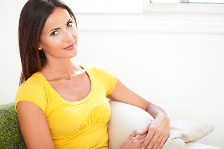 yellow shirt: Confident lady in yellow shirt looking at the camera while sitting on the couch