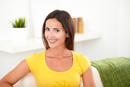 yellow shirt: Confident young woman in yellow shirt sitting on the couch while smiling at the camera Stock Photo