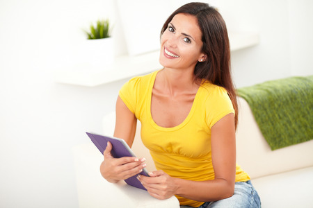 waist up: Waist up portrait of a peaceful young woman holding a tablet while sitting inside the house