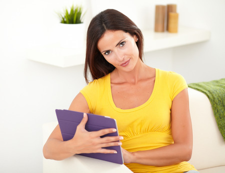 tank top: Seductive young woman in yellow tank top holding a tablet while looking at the camera Stock Photo