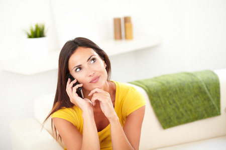 yellow shirt: Young woman in yellow shirt wondering while talking on cell phone - copy space