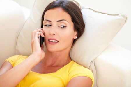 envious: Jealous woman speaking on cell phone while lying on her back at indoors