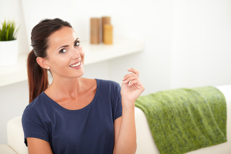 woman looking: Confident woman in blue shirt toothy smiling at the camera while sitting indoors - copy space
