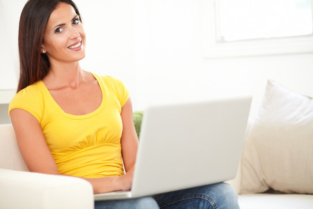 yellow shirt: Smiling student in yellow shirt using a laptop while sitting indoors