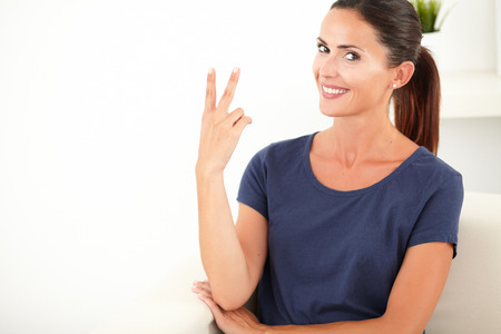 waist up: Waist up portrait of a happy woman in blue shirt making a victory sign