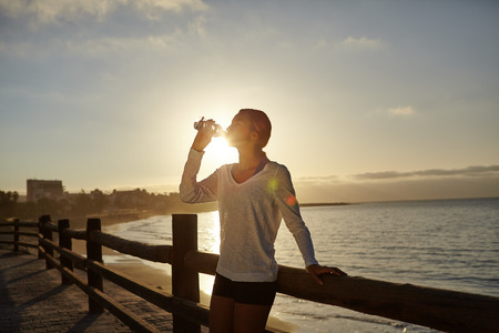 water activity: Young runner drinking from a water bottle near the beach at dawn - lens flare