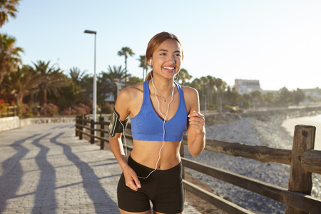 lifestyle outdoors: Smiling woman running on the coastline while living a healthy lifestyle