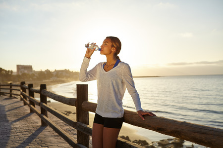 Young jogger drinking an energy drink outdoors in summertime with back lit Banque d'images