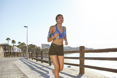 brightly: Fitness woman jogging on the coastline in day light with backround brightly lit