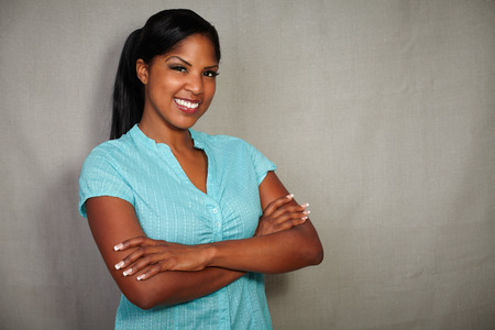 charismatic: Charismatic african lady smiling at the camera while standing with arms crossed Stock Photo