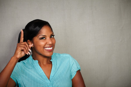 charismatic: Charismatic woman of afro-american ethnicity pointing up while smiling - copy space Stock Photo