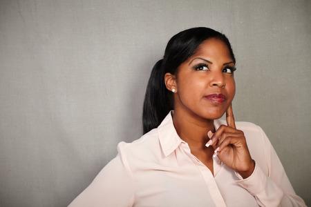 Mujer reflexiva de la etnia afroamericana contemplando con la mano en la barbilla Foto de archivo