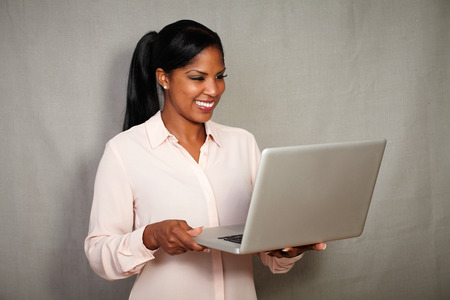 charisma: Young african businesswoman using a laptop against grey texture background - copy space