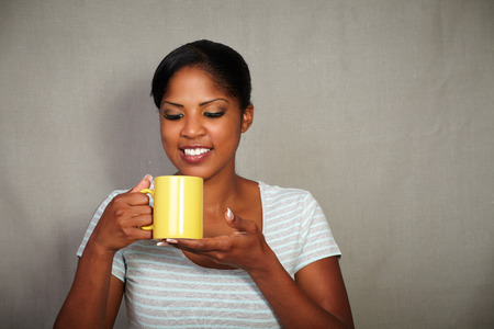 waist up: Waist up portrait of a happy girl holding a coffee cup while smiling - copy space