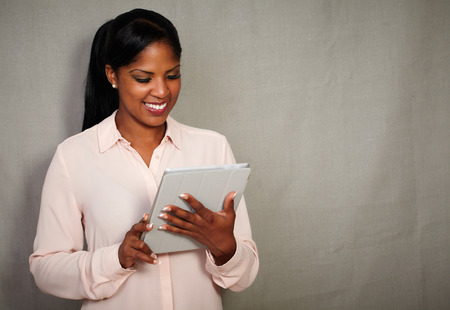 Young african businesswoman holding a tablet against grey texture background - copy space