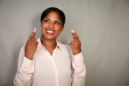 crossing fingers: Young businesswoman in button down shirt crossing fingers while smiling - copy space Stock Photo