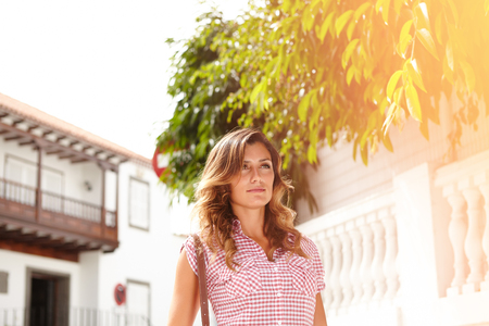Waist up portrait of a young woman with wavy hair walking outdoors during the day Stock Photo