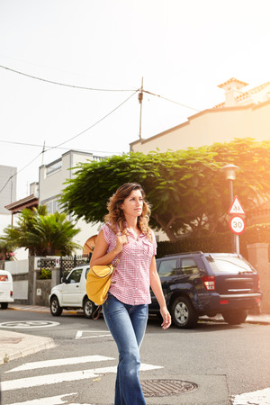 brightly lit: Young woman of caucasian ethnicity walking down a brightly lit street