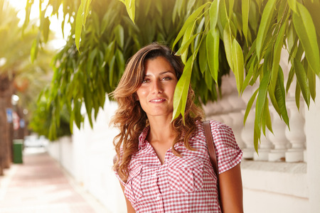 brightly lit: Caucasian lady in brightly lit day smiling at the camera through green branches