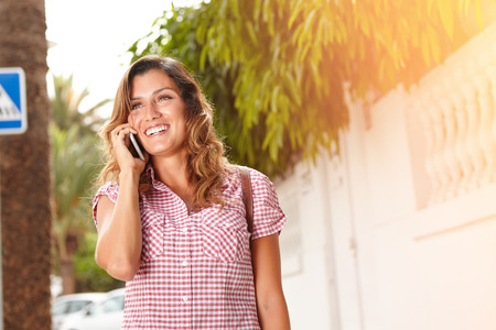 brightly lit: Young woman in brightly lit day smiling while talking on cell phone - focus on foreground with copy space