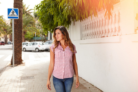 brightly: Young woman in brightly lit day smiling while walking outdoors - copy space