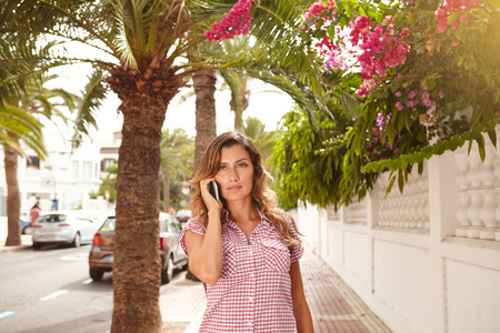 brightly lit: Beautiful woman in brightly lit day talking on cell phone outdoors Stock Photo
