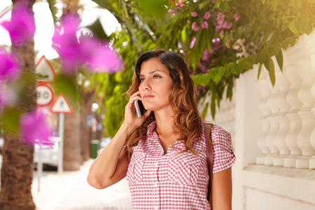 waist up: Waist up portrait of a confident lady listening to mobile phone outdoors Stock Photo