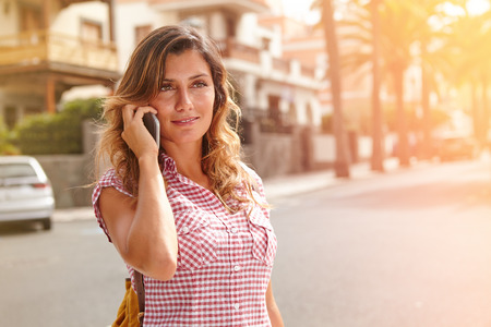 waist up: Waist up portrait of a young woman in brightly lit day speaking on cell phone down the street
