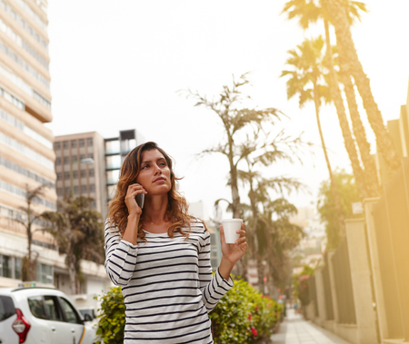 waist up: Waist up portrait of a young woman walking while holding a coffee cup and talking on mobile phone