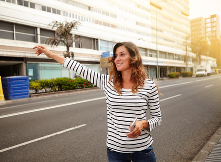 hailing: Cheerful young woman hailing a cab on city street while holding a smart phone - side view