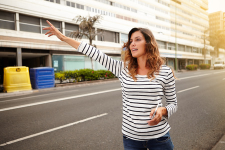 hailing: Side view of a young caucasian woman hailing a cab while holding a smart phone Stock Photo