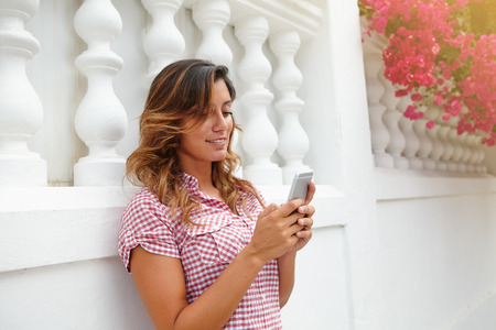 brightly lit: Cheerful lady smiling while using smart phone on brightly lit street - side view