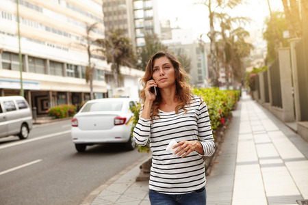 caucasian ethnicity: Young lady of caucasian ethnicity walking with confidence on city street and talking on cell phone