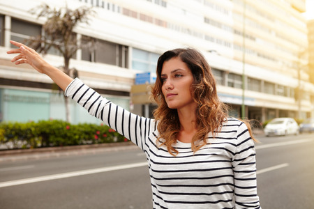 hailing: Waist up portrait of a beautiful woman of caucasian ethnicity hailing a cab during the day