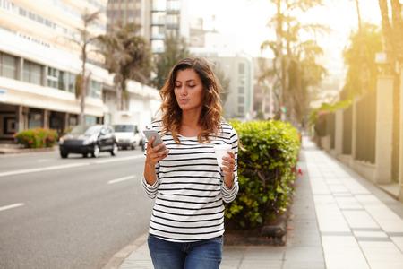 personas caminando: Hermosa mujer con teléfono inteligente mientras se camina en la avenida de la ciudad - se centran en primer plano
