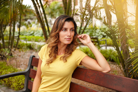 yellow shirt: Waist up portrait of a pensive woman in yellow shirt sitting on park bench