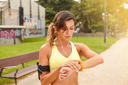 waist up: Waist up portrait of a young jogger looking at smart watch while standing outside