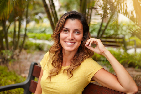 focus in foreground: Young woman with wavy hair smiling while sitting on park bench - focus on foreground Stock Photo