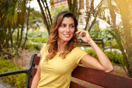 waist up: Waist up portrait of a cheerful lady in yellow shirt looking away while sitting on bench Stock Photo