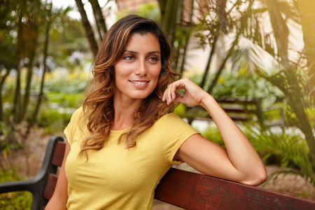 yellow shirt: Young caucasian woman in yellow shirt looking away with confidence while sitting outdoors