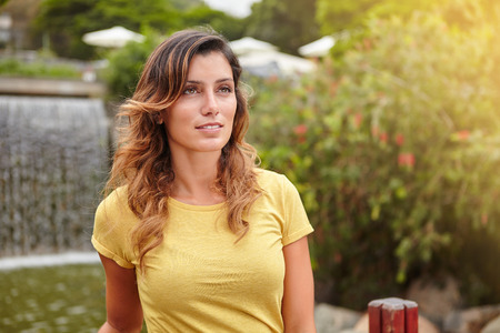 yellow shirt: Waist up portrait of a beautiful woman in yellow shirt standing by park waterfall