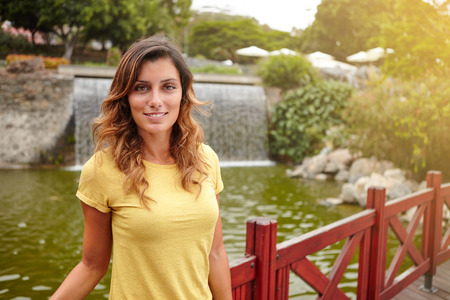 caucasian ethnicity: Beautiful woman of caucasian ethnicity smiling while standing near lake