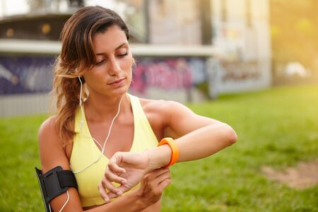 waist up: Waist up portrait of a young jogger listening to music while sitting outside Stock Photo