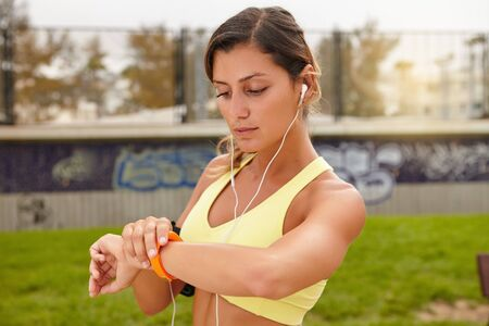 watch: Young athlete in tank top looking at smart watch outdoors Stock Photo